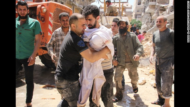 The father of a 3-month-old girl weeps Monday, May 26, after she was pulled from rubble following a barrel bomb strike in Aleppo.