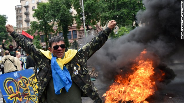 A protester from Kiev's Independence Square gestures May 31 as fellow protesters burn tires to protect their barricades from being dismantled by communal services.