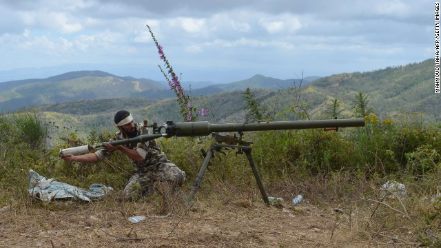 A rebel fighter loads an anti-tank cannon outside Latakia on Sunday, June 1.