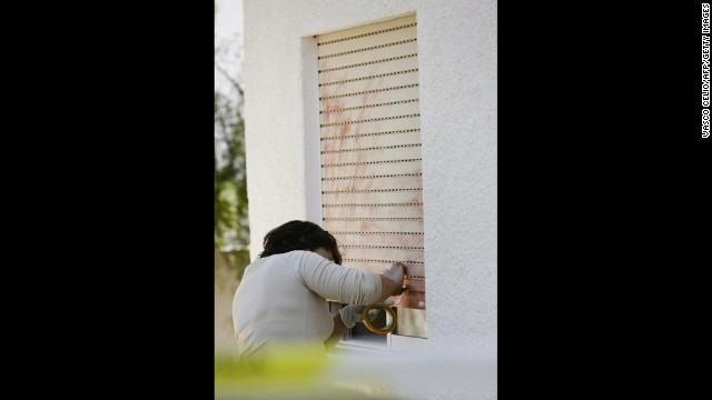 In this photo from 2007, a Portuguese police officer searches for evidence on the window that leads to the room where Madeleine was sleeping.