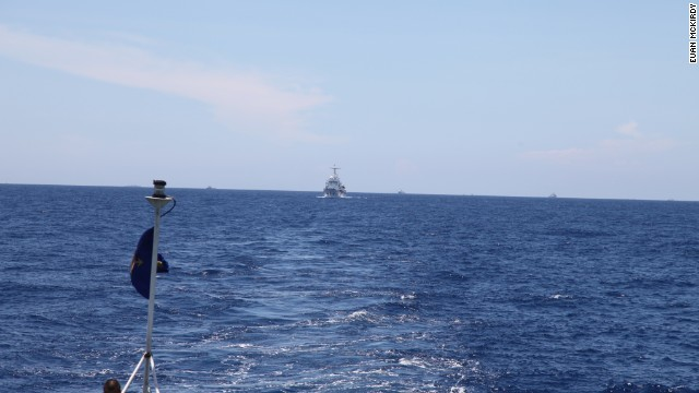 A Chinese Coast Guard vessel follows CG 8003 at a discreet distance.