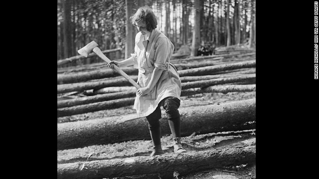 A member of the Women's Forestry Corps, part of the Women's Land Army in the United Kingdom, works circa 1916.