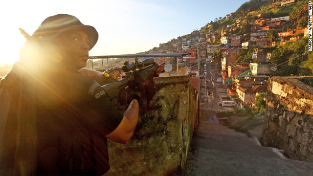 A police special forces officer holds his weapon during an operation in the Complexo do Alemao community, or 'favela' in Rio de Janeiro. Police in Brazil have forcibly occupied favelas in some of the country's biggest cities in the run up to the World Cup.