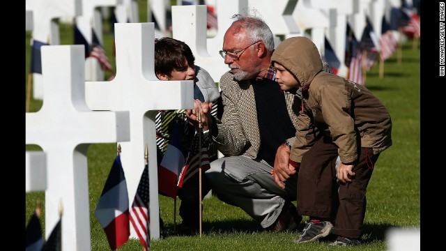 Michel Colas talks with his grandsons Samuel Colas and Rafael Schneider at the Normandy American Cemetery in Colleville-sur-Mer, France.
