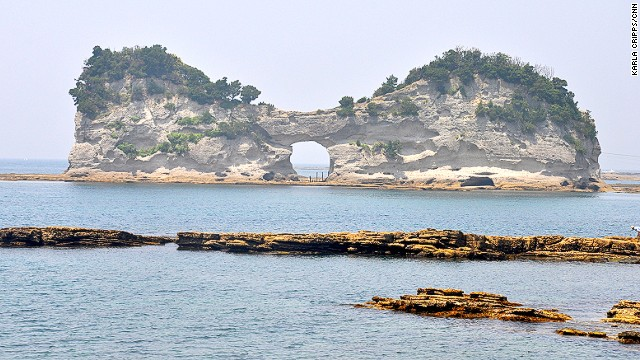 "Engetsu Island, off the coast of Shirahama, is a 130-meter-wide rock formation, famous for a moon-like hole in the middle. Designated a ""place of scenic beauty,"" it's easily viewed from the road on the mainland and is a favorite place for sunset shots."