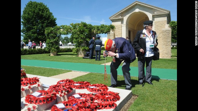 A British World War II veteran takes a picture of wreaths at the British War Cemetery in Bayeux, France.