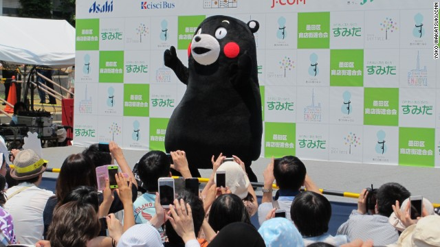 Kumamon, a rosy-cheeked silent black bear waves and dances to music as his fans snap photos. Kumamon is a ubiquitous presence in Japan, advertising everything from food and drinks to video games, and of course, his prefecture of origin, Kumamoto.