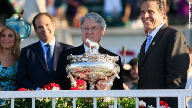 Owner of Tonalist, Robert S. Evans, is presented with the trophy from New York Gov. Andrew Cuomo after winning the race.