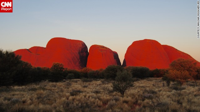 "<a href='http://www.parksaustralia.gov.au/uluru/people-place/amazing-facts.html' target='_blank'>Uluru-Kata Tjuta National Park</a> in Australia is home to one of the largest sandstone monoliths in the world. <a href='http://ireport.cnn.com/docs/DOC-1141663'>Anusha Mookherjee</a> says the park feels incredibly spiritual. From her experience, the best time to visit is at sunrise or sunset. ""It is extremely stunning at sunset when the rocks glow a deep, fiery red,"" she said."