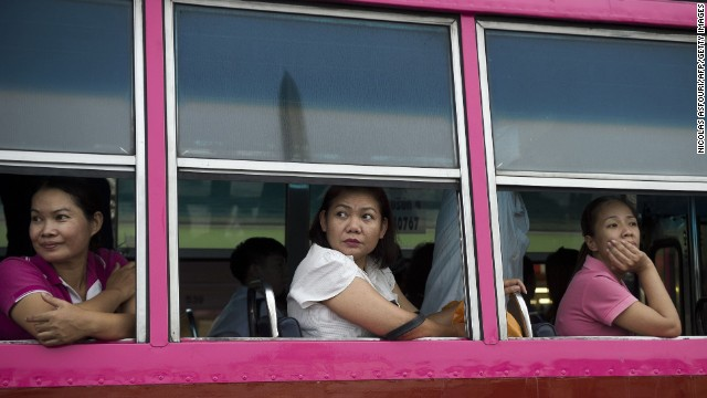 Passengers on a bus watch soldiers entertain the crowds at Bangkok's Victory Monument on June 5.