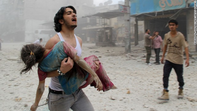 A man carries a girl injured in a reported barrel-bomb attack by Syrian government forces in Aleppo on June 3.
