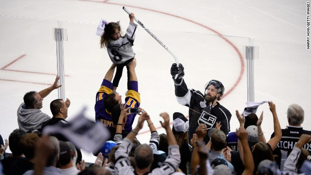 Justin Williams of the Los Angeles Kings hands his stick to a young fan after he scored the game-winning goal in Game 1 of the NHL's Stanley Cup Final. The Kings are looking to win their second Stanley Cup in three years.