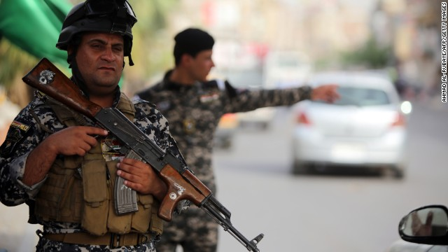 Iraqi police stand guard at a checkpoint in Baghdad.