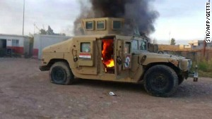 A picture taken with a mobile phone shows an armored vehicle belonging to Iraqi security forces in flames.