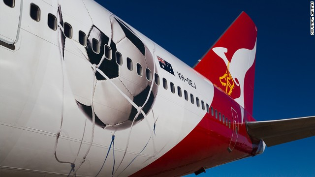 "Qantas is ""Proudly supporting the Socceroos"" with a Boeing 747 decorated with a large football and a pair of golden boots strung around the airline mascot's neck. No jokes about choking, please."
