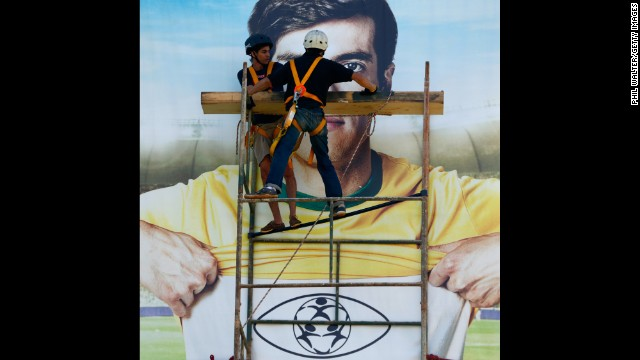 Construction workers put the finishing touches on banners outside of a stadium in Brasilia, Brazil.