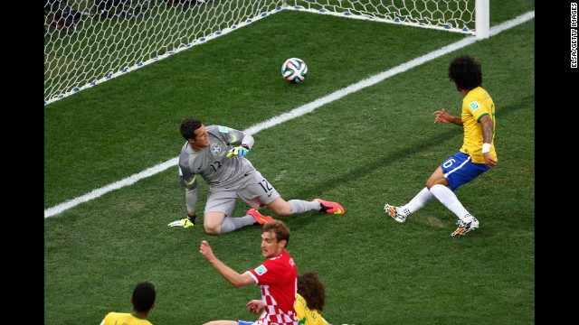 Marcelo, right, accidentally deflects the ball past his own goalkeeper, Julio Cesar. It was the <a href='http://www.cnn.com/2014/06/12/football/gallery/world-cup-goals/index.html'>first goal of the match</a> and put the hosts in an early hole. <a href='http://www.cnn.com/2014/06/12/football/gallery/world-cup-goals/index.html'>See all the goals from the World Cup</a>