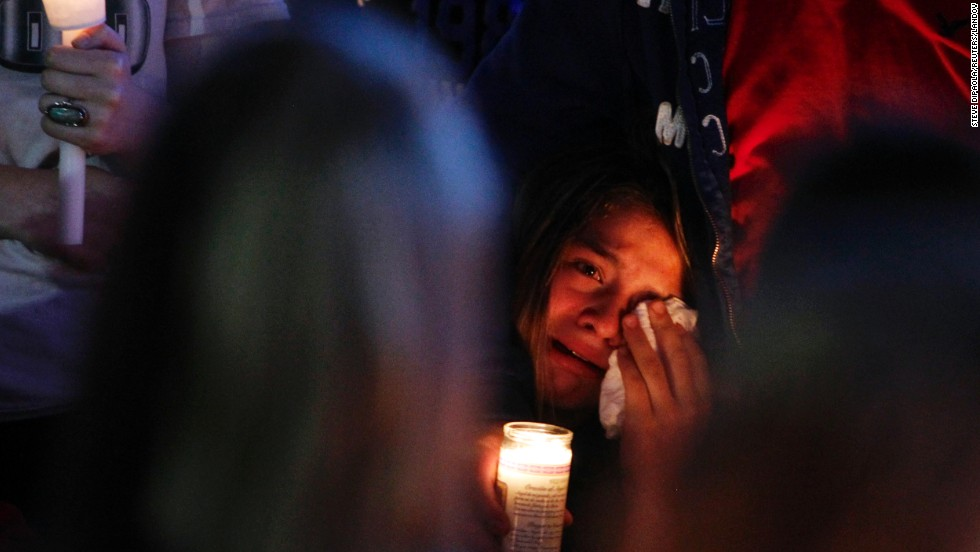 A mourner wipes away tears at a candlelight vigil after a <a href='http://www.cnn.com/2014/06/11/justice/oregon-high-school-shooting/index.html'>shooting took place</a> Tuesday, June 10, at Reynolds High School in Troutdale, Oregon. Jared Padgett, a 15-year-old student at the school, shot and killed another student, 14-year-old Emilio Hoffman, before taking his own life, law enforcement sources said. Padgett also shot and wounded a teacher.