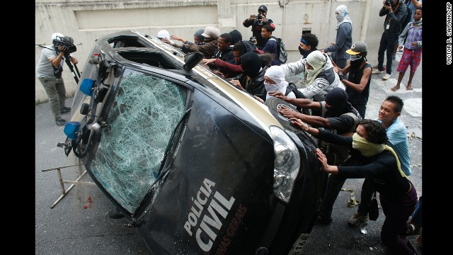 Demonstrators push over a police car.