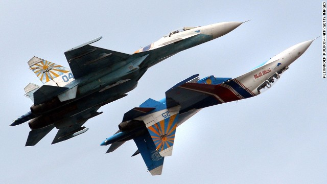 "A Russian Air Force flight demonstration team perform with their Su-27 jet fighters over St. Petersburg, Russia. An Su-27 ""showed its belly"" to a U.S. reconnaissance jet in April."