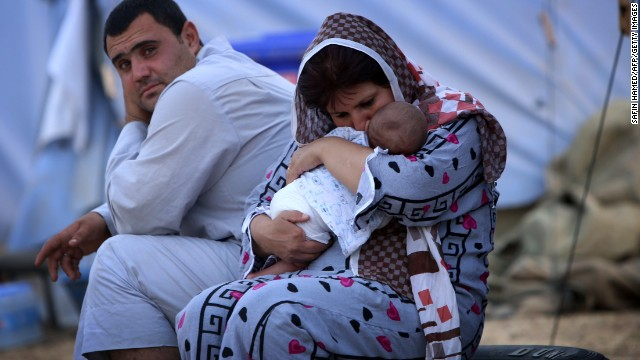 A woman cradles her baby Thursday, June 12, at a temporary camp set up in Aski Kalak, Iraq, to shelter those fleeing the violence in northern Nineveh province.