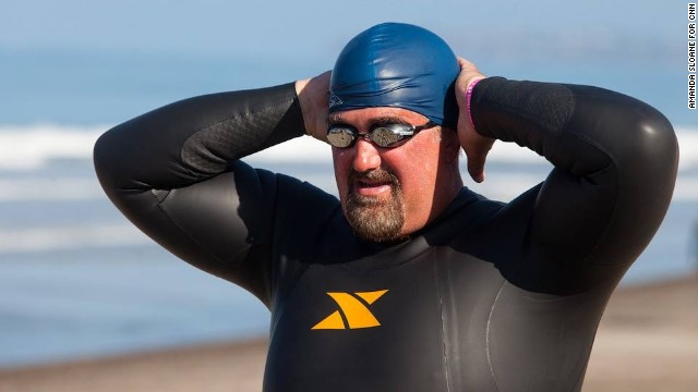 Fit Nation team member Mike Wilber adjusts his swim cap before entering the ocean in San Clemente, California.