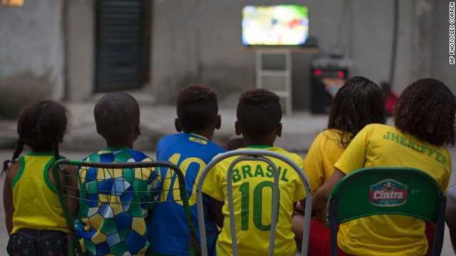 JUNE 13 - RIO DE JANEIRO, BRAZIL: Children watch the World Cup opening match between Brazil and Croatia in an alley at the Mangueira slum. Brazil secured a nervy 3-1 win. But thousands took to the streets in <a href='http://edition.cnn.com/2014/06/11/world/americas/brazil-world-cup-tent-city/'>protest against the government for spending $11 billion </a>on the tournament instead of housing, hospitals and schools.