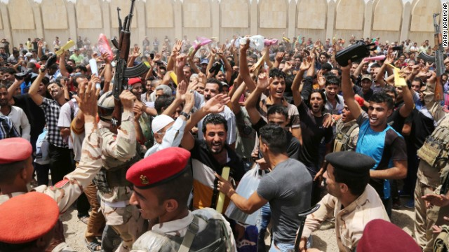 Iraqi men chant slogans outside of an army recruiting center to volunteer for military service Thursday, June 12, in Baghdad.