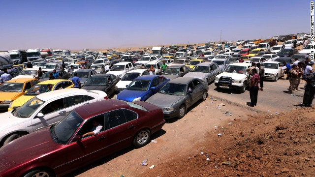 Iraqis fleeing the violence wait in their vehicles at a Kurdish checkpoint in Aski Kalak on June 10.