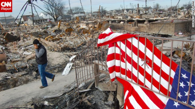 "An American flag drapes over the rails of a home that was ravaged by Superstorm Sandy in November 2012. <a href='http://ireport.cnn.com/docs/DOC-881311'>Paul Lurrie</a> visited the Breezy Point community in New York soon after the storm came through. ""I felt a bit like I was walking on sacred ground. I sensed a solemn and somber atmosphere, but this is a close-knit community,"" he said."