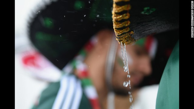 Rain drips off a Mexico fan's sombrero before the match. <a href='http://www.cnn.com/2014/06/12/football/galler
