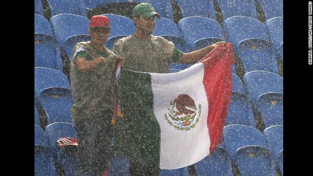 Mexico fans endure heavy rain as they wait for the start of the match.