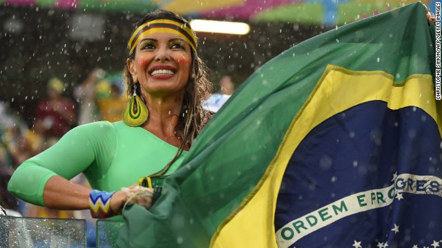 A fan holds a Brazilian flag during the match between Mexico and Cameroon.