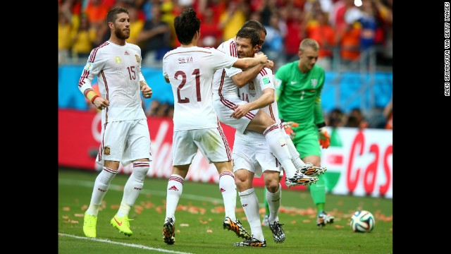 Alonso holds a teammate as Spain celebrates its first goal.