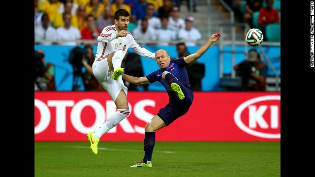 Spanish defender Gerard Pique, left, chases down Robben.