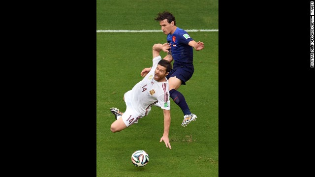 Alonso, left, falls near Dutch defender Daryl Janmaat.