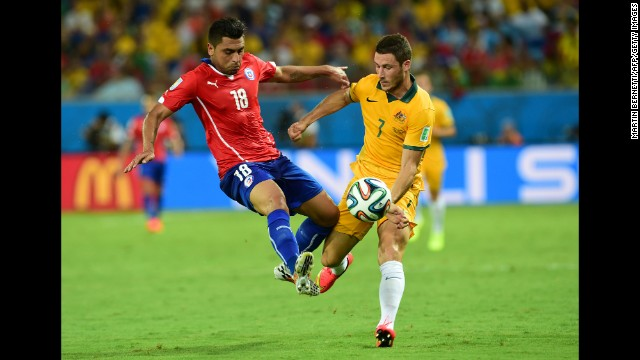 Chilean defender Gonzalo Jara, left, clashes with Australian forward Mathew Leckie.