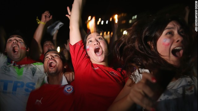 Chilean team fans react as they watch their team score against Australia on a giant screen showing the match at Copacabana Beach in Rio de Janeiro, Brazil.