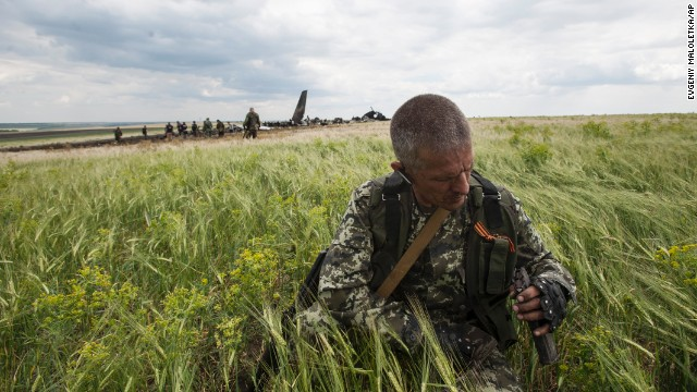 A pro-Russian fighter collects ammunition from the debris of the downed military aircraft on June 14.