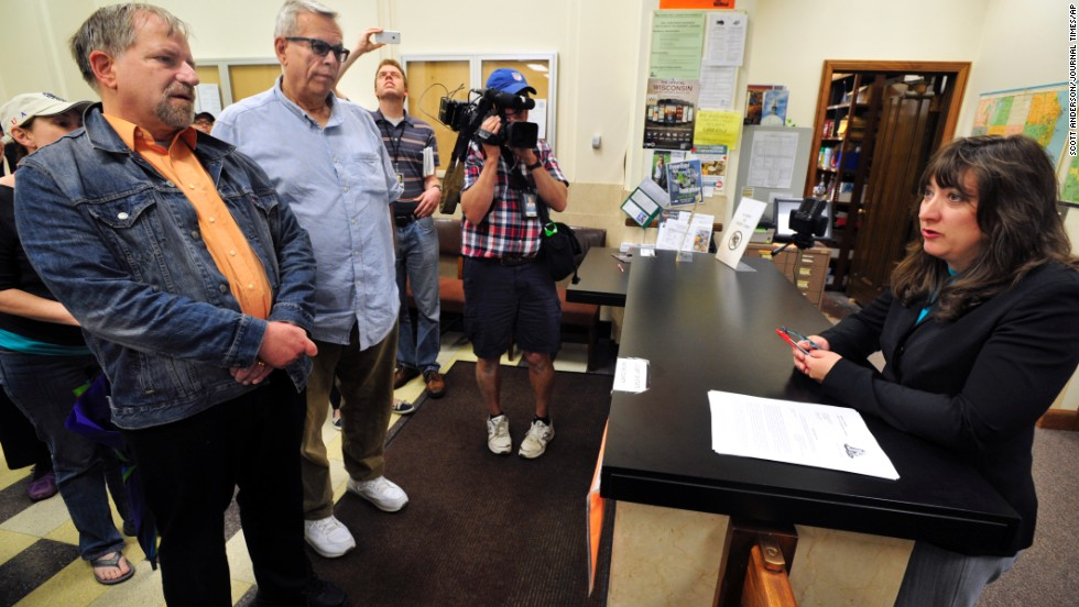 The Rev. Tony Larsen and his partner, Craig Matheus, are refused a marriage license by Racine County Clerk Wendy Christensen, right, in the clerk's office in Racine, Wisconsin, on Friday, June 13. The county does not grant marriage licenses to same-sex couples despite a judge's ruling that the state ban on gay marriage is unconstitutional.