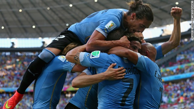 Martin Caceres piles on his Uruguay teammates as they celebrate Cavani's first-half goal.
