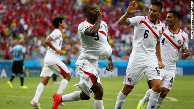 Joel Campbell of Costa Rica, left, celebrates scoring his team's first goal with the ball under his jersey as teammates Oscar Duarte, center, and Michael Umana run on.
