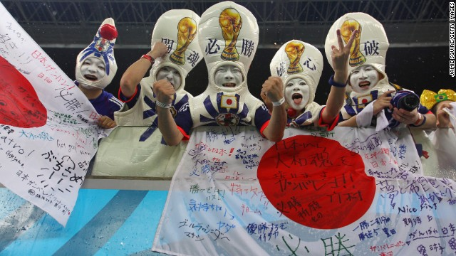 Japan fans proudly display flags and cheer during the match.