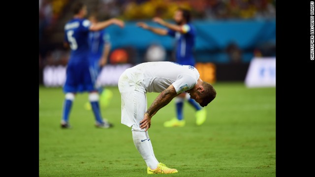 A dejected Jack Wilshere of England looks down as Italy celebrates the win.
