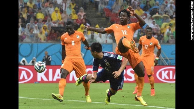 Japan forward Shinji Okazaki, center, heads the ball past Ivory Coast forward Wilfried Bony.