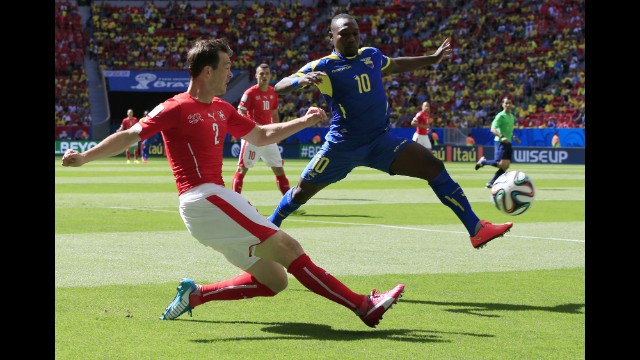 Switzerland defender Stephan Lichtsteiner, left, crosses the ball past Ecuador midfielder Walter Ayovi.