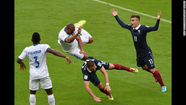 Honduras defender Victor Bernardez, center, falls over France forward Karim Benzema.