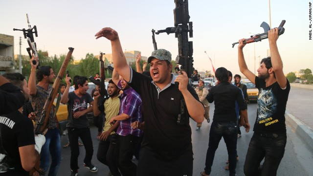 Shiite tribal fighters raise their weapons and chant slogans against ISIS in Basra, Iraq, on June 15.