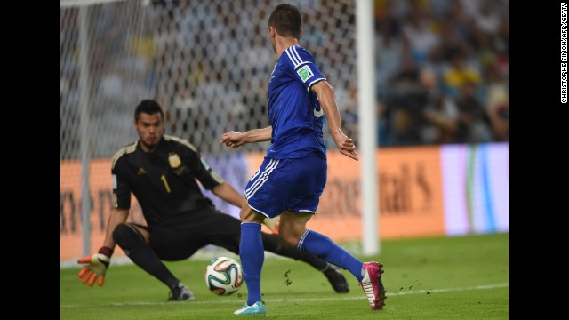 Substitute Vedad Ibisevic shoots past Argentina goalkeeper Sergio Romero to score Bosnia-Herzegovina's historic first World Cup goal Sunday, June 15, at the Maracana Stadium in Rio de Janeiro. But Argentina won the match 2-1.
