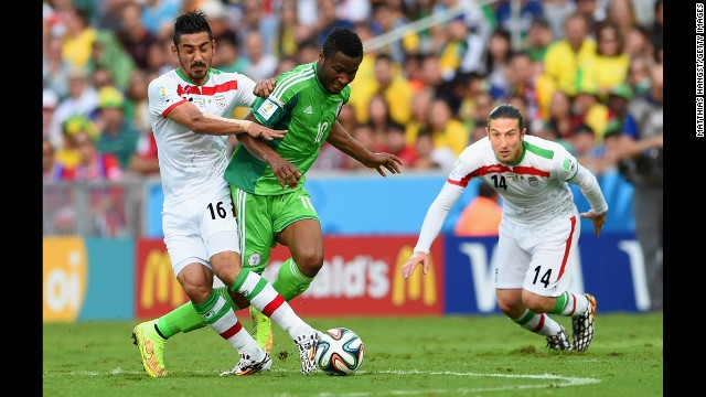 John Obi Mikel of Nigeria, center, tries to tackle Iran's Reza Ghoochannejhad.